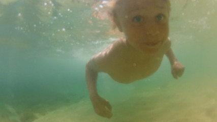 boy is swimming under water in the sea