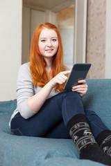 girl with e-book on sofa