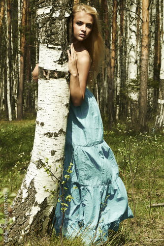 Beautiful blond woman in summer forest