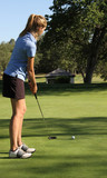 Female teen golfer putting on green