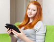 Teenager girl reads e-reader or tablet computer