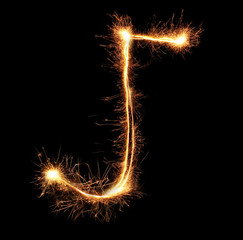 "Letter ""J"" sparklers on black background"