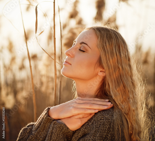 Portrait of a smiling blond woman relaxing outdoors in a autumn