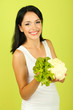 Girl with fresh cauliflower on green background