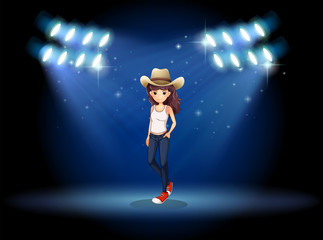 A lady wearing a hat standing at the stage under the spotlights