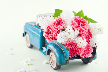 Toy truck carrying pink carnation and lilacs flowers