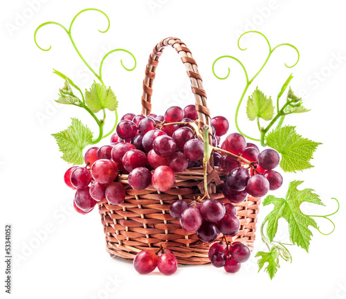 Red grapes in wicker basket with leaves Isolated on white