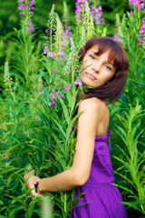 Beautiful young woman posing against a background of green grass
