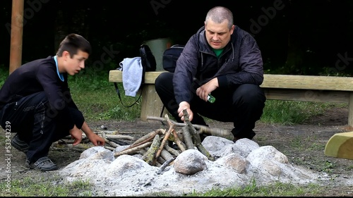 Father and son piling firewood for campfire episode 2