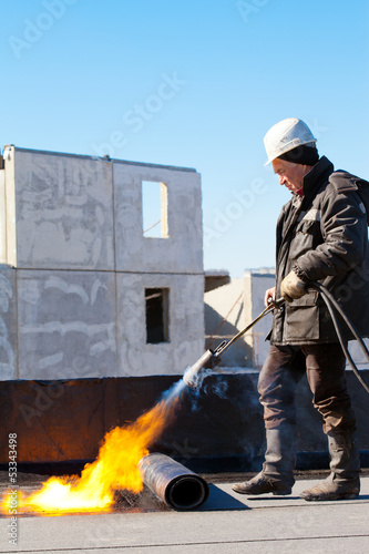 Roofer installing roll of roofing felt using gas blowpipe torch