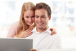 Young smiling couple purchasing on internet