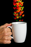 Hand holding white cup with bokeh heart shapes