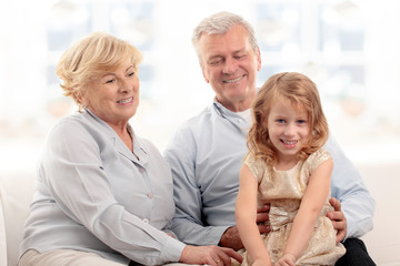Grandparents laughing with granddaughter