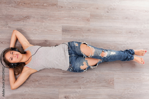 Woman lying on a floor with headphones