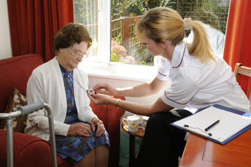 Healthcare visitor helping an elderly lady alarm