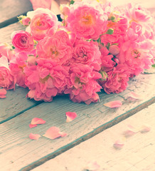 Gentle pink roses on wooden table