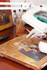 Art restorer working on the old icon