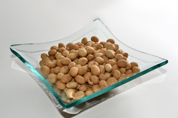 Fresh salted crispy peanuts in a decorative moden glass dish