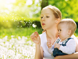happy family. Mother and baby girl blowing on a dandelion flower