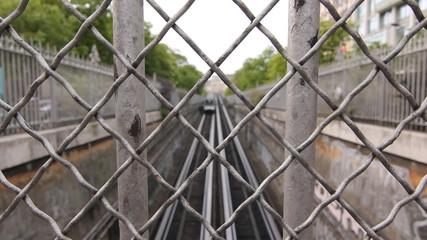 Paris metro train through fence. Two shots.