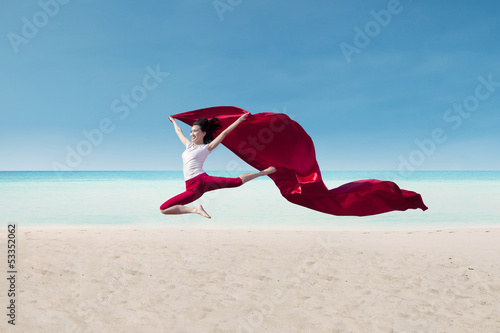 Beautiful dancer with red flag at beach