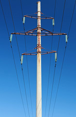 High voltage power lines and pylon above blue sky
