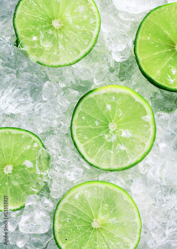 Slices of green limes over crushed ice cubes - 53353821