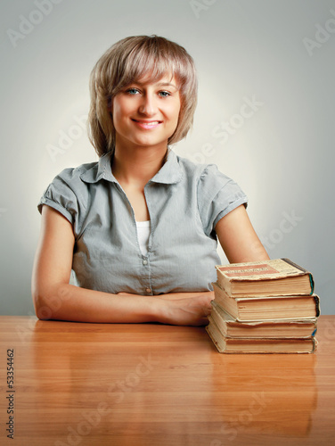 young woman sitting on the desk with pile