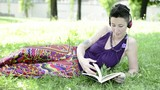 beautiful hipster short hair woman reading book in the park