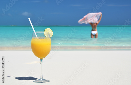 Glass of orange juice on the sandy beach of Exuma, Bahamas
