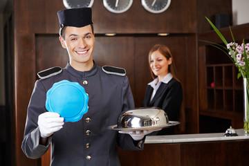 Hotelpage hält leeres Schild an Rezeption