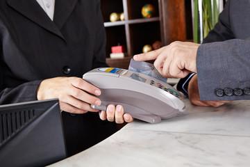 Hand zieht Kreditkarte durch EC-Terminal