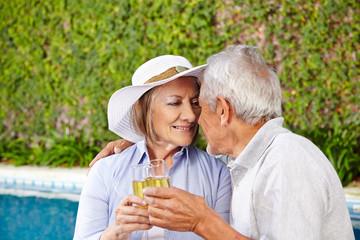 Zwei Senioren mit Sekt am Pool