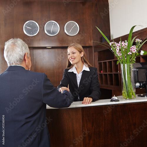 Empfangsdame begrüßt Senior im Hotel