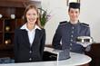 Leinwandbild Motiv Hotelpage und Empfangsdame an Rezeption