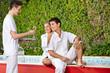 Paar am Pool bekommt Sekt vom Kellner