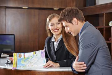 Empfangsdame im Hotel hilft Gast mit Stadtplan
