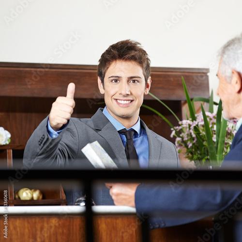 Concierge in Hotel hält Daumen hoch