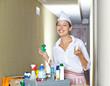 Zimmermädchen mit Putzmitteln im Hotel im Flur