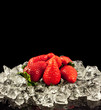 strawberry on black background.  strawberries with ice cubes on