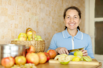 Woman cuts apples for apple jam