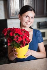 young woman keeps a flower in a pot