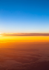 Dramatic sunset.  View of sunset above clouds from airplane wind
