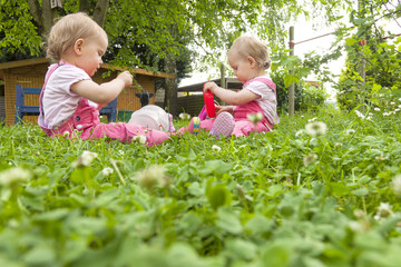 identical twin sisters picking clover