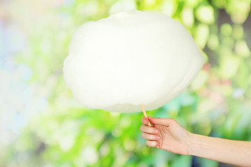 Hand holding stick with cotton candy, on bright background