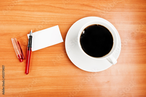coffee cup, piece of paper and pen on the wooden table