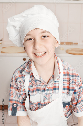 portrait of a happy little chef in a cap and apron in the