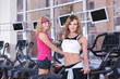 Two beautiful women smiling on treadmill in gym
