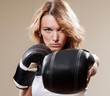 Portrait of blonde sportish woman in boxing gloves