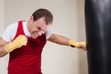 Man in boxing gloves makes a series of exercises punching bag